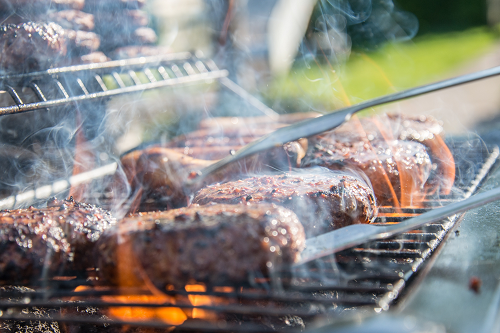 a close up of burgers being cooked on a grill